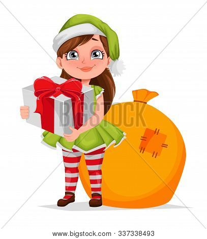 Merry Christmas Greeting Card. Cheerful Girl In Costume Of Elf Holding Gift Box. Kid In Santa Claus