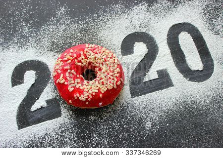 Text 2020 surrounded by colorful donuts on a black background vintage, new year concept. New year, C