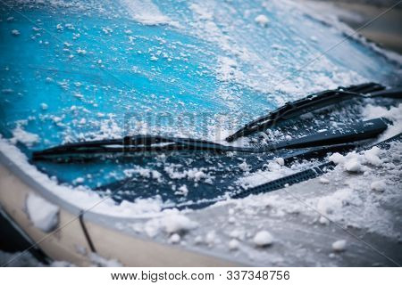 In Cold Snowy Winter Weather, The Car Cleans Its Windshield, Covered With Frost And Snow, Wipers.