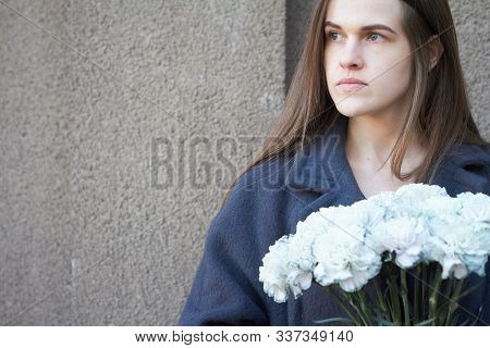 Girl With Dark Hair Holds In Her Hands A Bouquet Of Blue Carnations On A Gray Wall Background, Selec