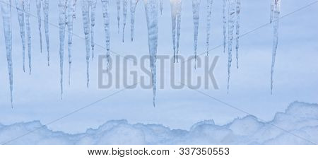 Icicles Hanging Down Over The Snowy Winter Background Covers Close-up