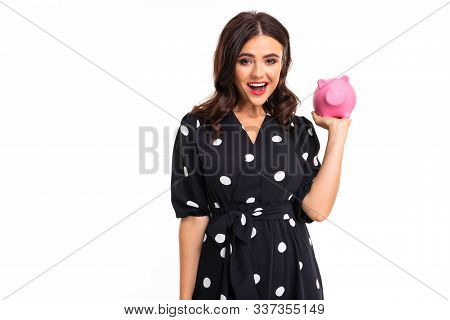 European Attractive Girl In Dress Holds A Piggy Bank In Hands On A White Studio Background With Copy