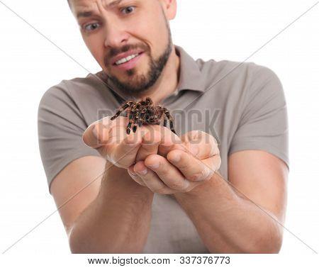 Scared Man Holding Tarantula On White Background. Arachnophobia (fear Of Spiders)