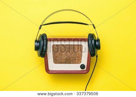 Black Headphones With Wire And Vintage Radio On Yellow Background. Radio Broadcast Live. Vintage Tec