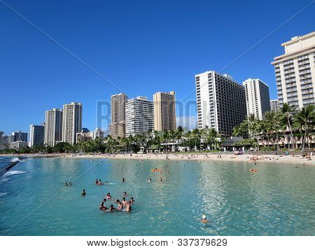 Waikiki, Hawaii - November 8, 2014: People Play In The Protected Water And Hang Out On The Beach In