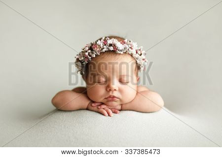 Newborn In  Floral Headband On The Blankets Folded Handles.