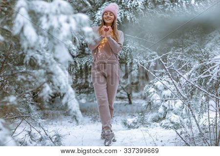 Woman 30-35 Years Old In A Warm Tracksuit On The Background Of A Snowy Forest With Christmas Trees.