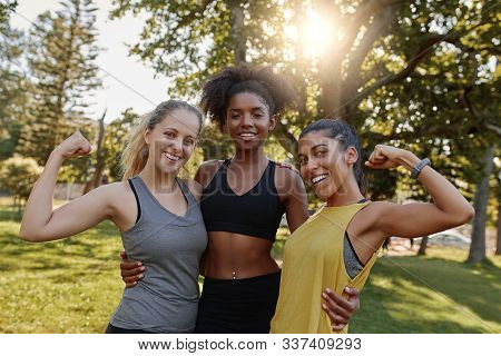 Portrait Of An African American Female Woman Standing With Her Two Diverse Friends Flexing Their Mus