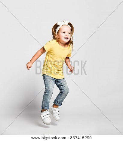 Cheerful Happy Kid Baby Girl Blonde In Yellow T-shirt, Blue Jeans And Sneakers Is Jumping High, Havi