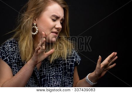 Portrait Of Blonde Girl On A Dark Studio Background, Hands And The Face Of Expresses Discontent, Dis