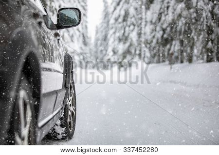 Car on a snowy winter road amid forests - using its four wheel drive capacities to get through the snow