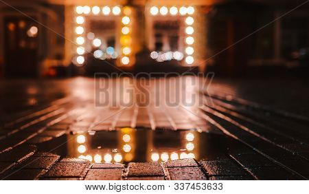 Rainy Night In A Big City, Reflection Of Colorful City Lights On The Wet Road Surface. The View From