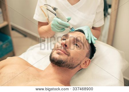 Hand In Rubber Gloves Nourishing The Skin Of Man
