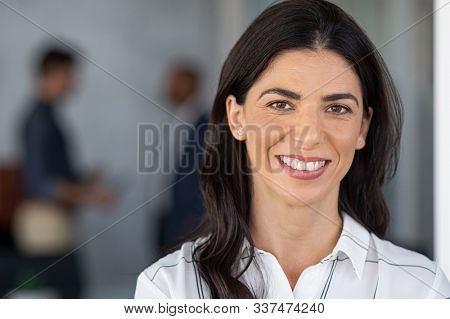 Portrait of mature businesswoman looking at camera with colleague in background. Close up face of successful latin business woman in modern office smiling. Confident and realiable middle aged woman.