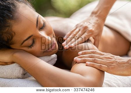 Young woman in spa salon getting massage. Closeup hands of masseuse doing massage on girl shoulder. Beautiful relaxed woman receiving beauty treatment at resort spa.