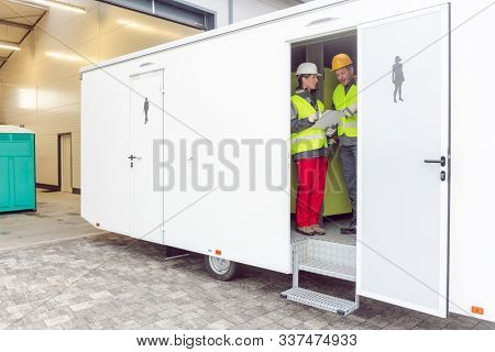 Workers inspecting a restroom trailer before renting it out to the customer