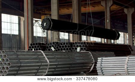 Metal Pipes In A Warehouse, Close Up. Stacks Of New Round And Shiny Steel Pipes In Metalworking Fact