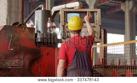 An Employee In Helmet Operating A Metal Processing Machine That Manufactures Sheet Metal For Further