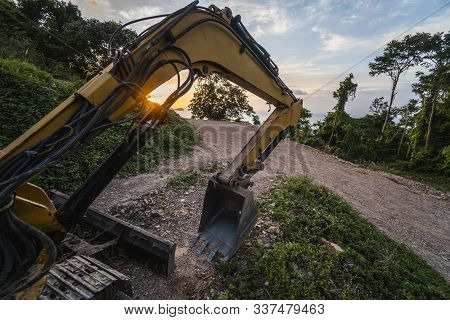 The Modern Excavator On The Construction Site With Sunset Sky. Large Tracked Excavator Standing On A