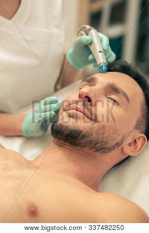 Relaxed Young Man Enjoying Skin Nourishing Procedure