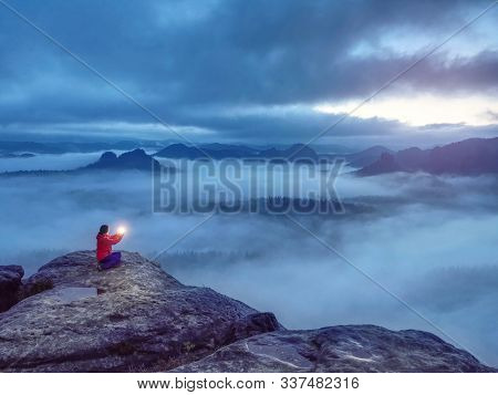 Lost Girl Sit On Rocky Peak In  Darkess Holding In Hands Symbol Of Hope. Cold Mist Night Above The W