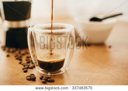 Pouring Hot Coffee In Glass Cup On Background Of Roasted Coffee Beans, Grounded Coffee, Geyser Coffe