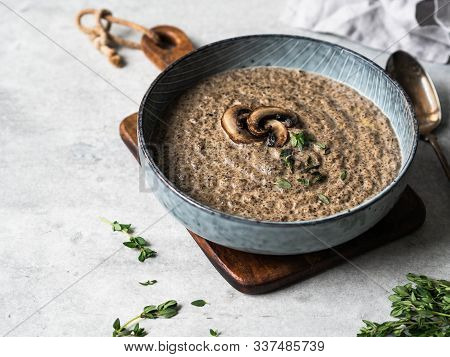 Champignon Mushroom Cream Soup With Fresh Thyme In Blue Bowl On Wood Cutting Board.