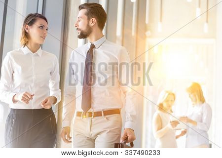 Business people discussing plans while walking in office hall before meeting against colleagues with yellow lens flare