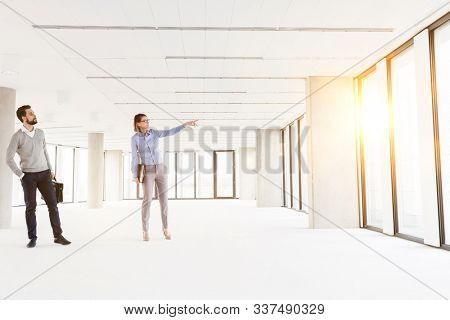 Businesswoman showing new office interior to businessman with yellow lens flare