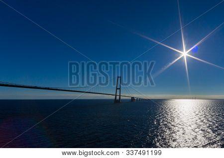 Oresund Bridge With Deep Blue Ocean, Sky, Sun And Light Reflexes