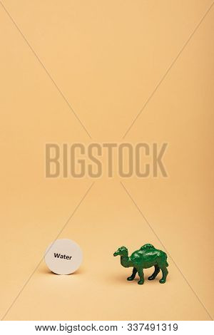 Green Toy Camel With Lettering Water On Card On Yellow Background, Water Scarcity Concept