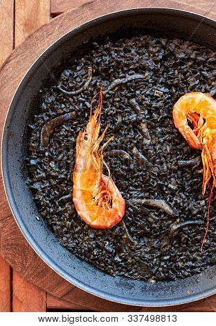 Spanish Black Rice With Cuttlefish And Prawns, Called Arroz Negro, On A Rustic Wooden Board.