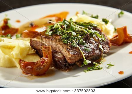 Beef brisket and mashed potato on white plate. Homemade delicious rural food. Baked meat piece with forest mushrooms and herbs side view. Vegetable puree with pork meal on black table