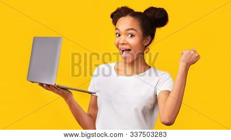 Celebrating Success. Portrait Of Excited African American Girl Holding Laptop Computer At Studio. Pa