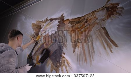 Artist Designer Draws An Eagle On Wall. Craftsman Decorator Paints Picture With Acrylic Oil Color Lo