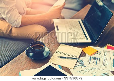 Book, Paper Graph And Laptop And Coffee On The Table Near Businessman Sitting On Sofa.