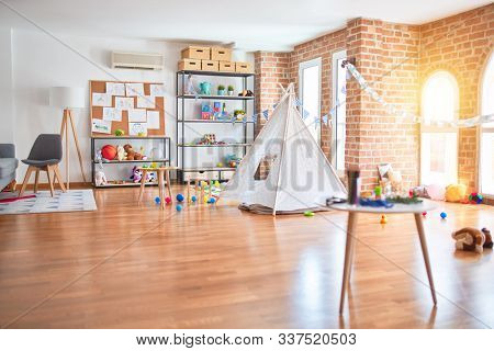 Picture of preschool playroom with colorful furniture, and toys around empty kindergarten