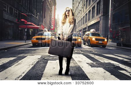 Beautiful woman standing on a crosswalk and holding a suitcase