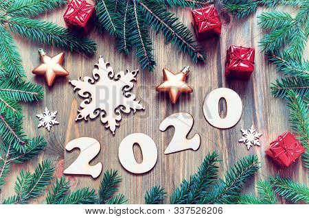 New Year 2020 card. New Year 2020 background with 2020 figures, Christmas toys, green fir tree branches on the wooden background. New Year 2020 festive still life in vintage tones