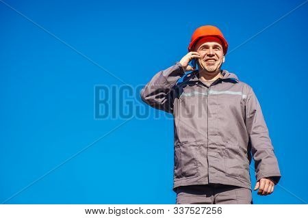 Construction Worker In A Helmet Against The Blue Sky Talking On The Phone. Contractor Control Accord