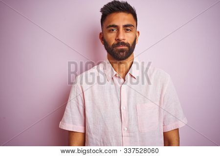 Young indian man wearing casual shirt standing over isolated pink background Relaxed with serious expression on face. Simple and natural looking at the camera.