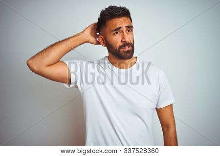 Young indian man wearing t-shirt standing over isolated white background confuse and wondering about question. Uncertain with doubt, thinking with hand on head. Pensive concept.