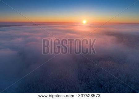 Winter Scenic Background. Aerial Winter Landscape With Snowy Forest And Pink Violet Fog Under Clear