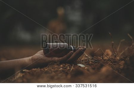 Concept Of Farmer Suicide, Closeup Of Hands With Poison Bottle At Farm Or Agriculture Land.