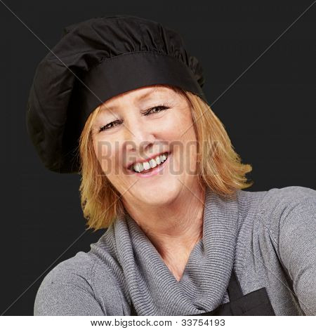 portrait of a middle aged cook woman smiling over a black background poster