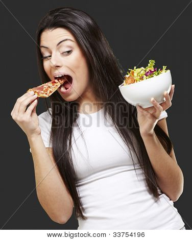 woman choosing a slice of pizza instead of a salad against a black background