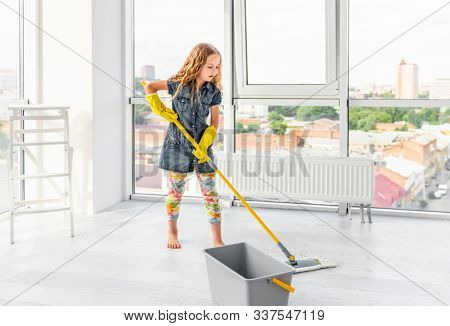 Pretty little girl in yellow rubber gloves mopping