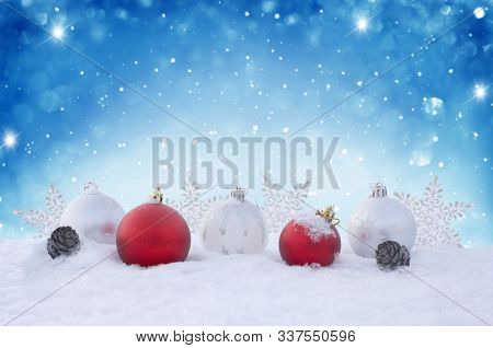 Holiday background with red Christmas balls, snowflakes and  cones. Winter Scene. New Year greeting card. Christmas decorations on the snow.