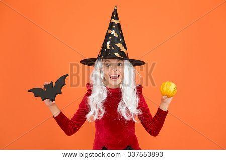 Freakishly Wicked Halloween. Little Wicked Witch Child Hold Bat And Pumpkin. Happy Girl Wear Wicked