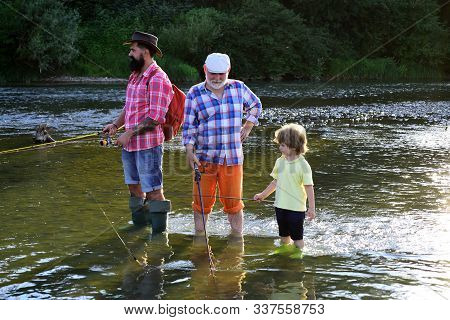 Man With His Son And Father On River Fishing With Fishing Rods. Boy With Father And Grandfather Fly